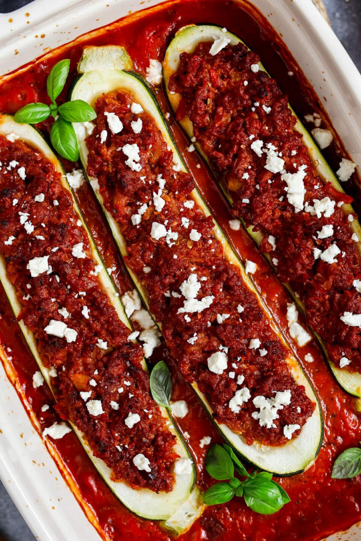 Gefüllte Zucchini mit veganem Hackfleisch in Tomatensauce, serviert in einer Auflaufform