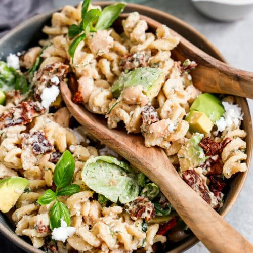 Veganer Nudelsalat mit weißen Bohnen, angerichtet mit Basilikum in einer tiefen Schüssel