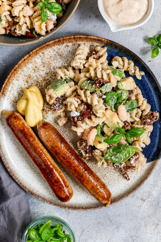 Veganer Nudelsalat mit weißen Bohnen, angerichtet mit Basilikum und veganen Würstchen auf einem flachen Teller
