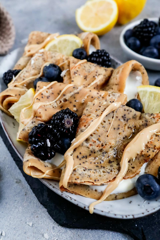 Vegane Zitronen Mohn Crêpes Blaubeeren und Brombeeren, angerichtet auf einem hellen Teller
