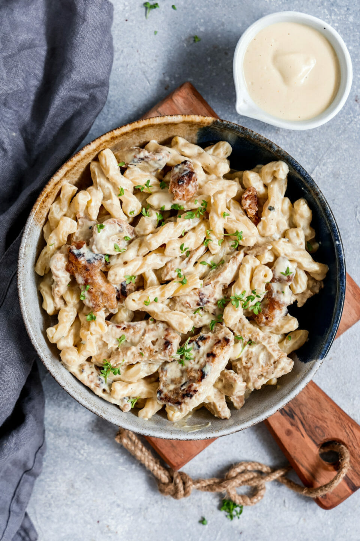 Cremiges, veganes Chicken Alfredo serviert in einem tiefen Teller auf einem Holzbrett