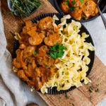 Vegane Champignon Rahm Sauce mit Nudeln in einem tiefen, dunklen Teller - garniert mit Petersilie