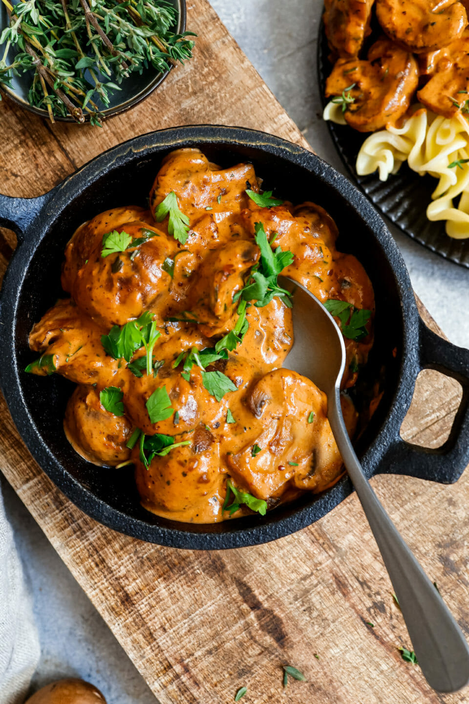Vegane Champignon-Rahm-Sauce mit Nudeln in einem tiefen, dunklen Teller - garniert mit Petersilie