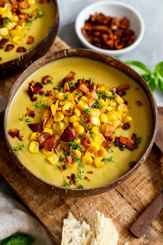 Vegane Maissuppe mit Kokos-Speck angerichtet in einer Schüssel mit etwas Weißbrot, Kresse und frischem Basilikum