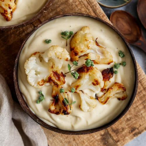 Vegane Blumenkohl Suppe serviert in zwei Kokosschalen mit ofengeröstetem Blumenkohl.