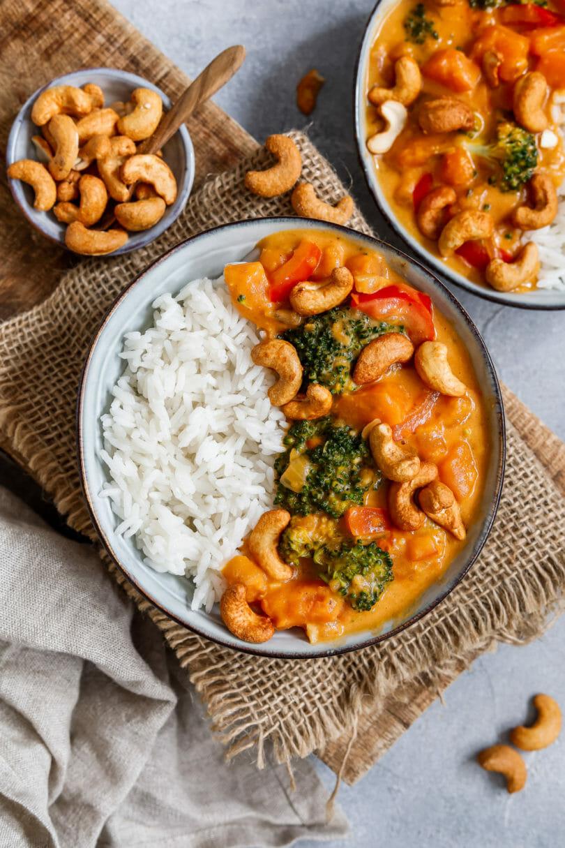 Veganes Süßkartoffel Curry mit Brokkoli serviert mit Reis und Cashews in einem tiefen Teller
