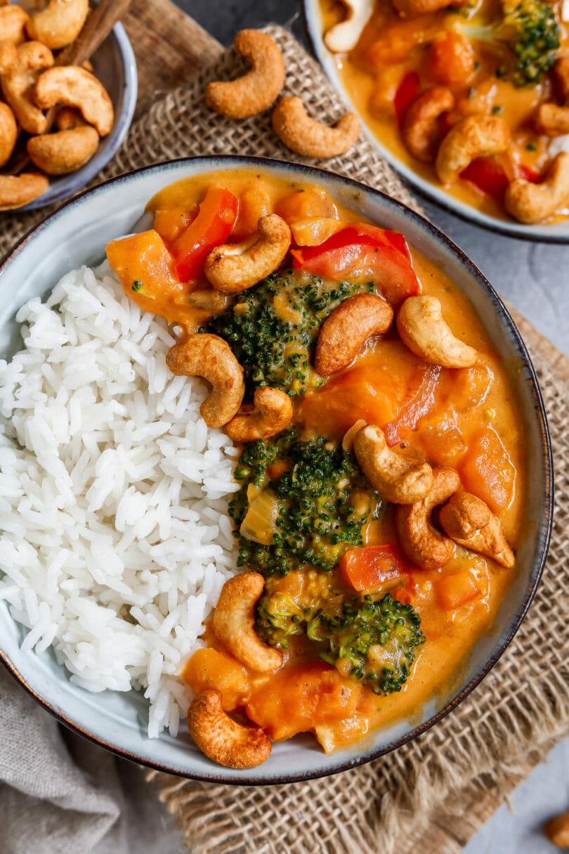 Veganes Curry serviert in einem tiefen Teller auf hellem Untergrund, dazu Brokkoli, Süßkartoffeln und Cashewkerne