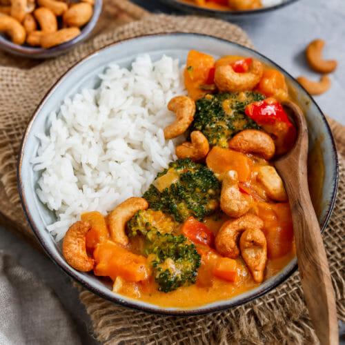 Cremiges Brokkoli Curry serviert in einem tiefen Teller mit Süßkartoffeln, Paprika und getoppt mit Cashewnüssen