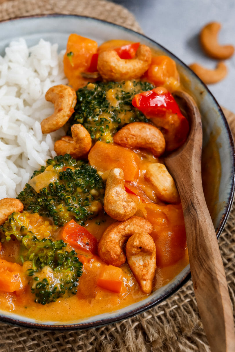 Ein Curry bestehend aus Brokkoli, Paprika, Süßkartoffeln und getoppt mit Cashewkernen in einem tiefen Teller - dazu gibt es Kokos-Reis